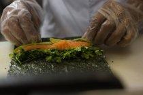 Середине секции старших шеф-повар готовит суши в ресторане кухня — стоковое фото