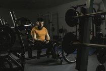 Инвалид проверяет смартфон на прессе в спортзале — стоковое фото