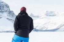 Вид сзади мужчин альпиниста, стоящего на снежные горы в зимнее время — стоковое фото