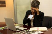 Зрелая деловая женщина разговаривает по мобильному телефону в офисе — стоковое фото