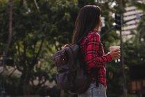 Vista laterale della donna con tazza di caffè in piedi sulla strada — Foto stock