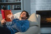 Hombre leyendo un libro mientras se está acostado en el sofá en la sala de estar en casa - foto de stock