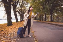 Businesswoman hailing on side of road during autumn — Stock Photo