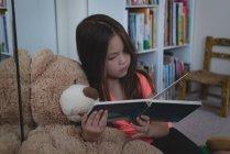 Niño en edad primaria con oso de peluche, lectura en sala de estar en casa - foto de stock