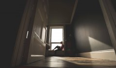 Mujer leyendo libro en ventana alféizar en casa - foto de stock