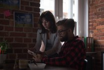 Cadres masculins et féminins discutant sur tablette numérique au bureau — Photo de stock