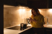 Woman using mobile phone in kitchen at home — Stock Photo