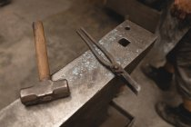 Close-up of hammer and pliers on anvil in workshop — Stock Photo