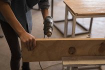 Mid section of craftswoman using drilling machine in workshop. — Stock Photo