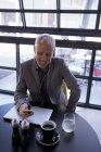 Бізнесмен, що використання мобільного телефону під час роботи над ноутбук у готельному фойє — стокове фото