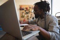 Carpinteiro usando laptop à mesa na oficina — Fotografia de Stock