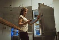 Mulher usando tablet digital ao abrir uma geladeira em casa — Fotografia de Stock