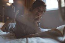Femme lisant un livre dans une chambre à la maison — Photo de stock