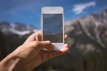 Close-up of man taking photo of mountains with mobile phone — Stock Photo