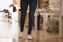 Low section of female executive walking on wooden floor in the creative office — Stockfoto