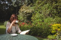 Femme lisant le livre tout en buvant le café dans le jardin — Photo de stock