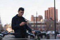 Чоловік стоїть поруч з його велосипед і використання мобільного телефону на вулиці — стокове фото