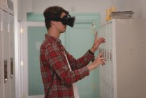 Male executive using virtual reality headset in creative office — Stock Photo