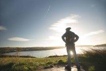 Vista posterior de hombre caminante junto a río en el campo - foto de stock