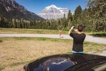Homme prenant une photo de femme avec téléphone portable par une journée ensoleillée — Photo de stock