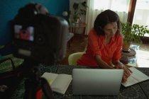 Femme blogueur vidéo écrit sur le journal devant la caméra à la maison — Photo de stock