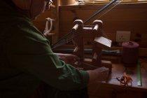 Активные старший женщина, ткачество шелка в магазине — стоковое фото