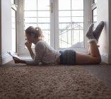 Donna che utilizza tablet digitale mentre sdraiato sul pavimento a casa — Foto stock