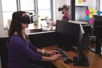 Female executive using virtual reality headset with computer at desk in office — Stock Photo