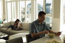 Père ayant le petit déjeuner et les filles à l'aide de tablette numérique à la maison — Photo de stock