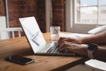 Primer plano de la ejecutiva femenina utilizando el ordenador portátil en la oficina creativa - foto de stock