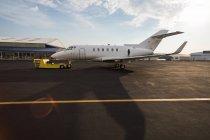 Частный реактивный самолет с тележкой на терминале в солнечном свете — стоковое фото
