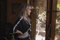 Femme mûre réfléchie regardant par la fenêtre à la maison — Photo de stock