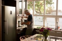 Senior man pouring coffee in kitchen at home — Stock Photo