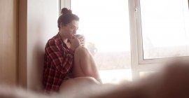 Femme réfléchie buvant du café sur le rebord de la fenêtre à la maison . — Photo de stock