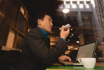 Low angle view of businessman talking on mobile phone in coffee shop — Stock Photo