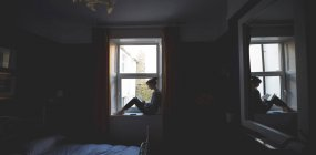 Frau liest Buch auf Fensterbank im Schlafzimmer zu Hause — Stockfoto