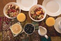 Vista di alto angolo di colazione e succo sul tavolo a casa. — Foto stock