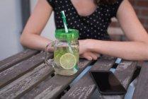 Gros plan du jus de citron et téléphone portable sur une table — Photo de stock