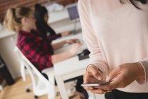 Esecutivo femminile utilizzando il telefono cellulare nell'ufficio creativo — Foto stock