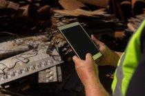 Close-up de trabalhador, usando um tablet digital no ferro-velho — Fotografia de Stock