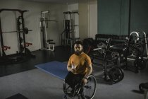 Young handicapped man on wheelchair with water bottle in gym — Stock Photo