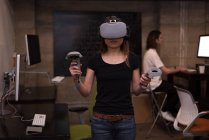 Female executive using virtual reality headset with controller in office interior. — Stock Photo