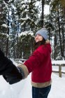 Couple holding hands in snow forest during winter — Stock Photo