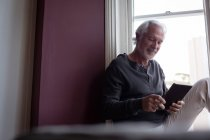 Homme senior à l'aide de tablette numérique près de fenêtre dans la salle de séjour à la maison — Photo de stock
