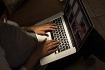 Mujer usando portátil en la sala de estar en casa - foto de stock