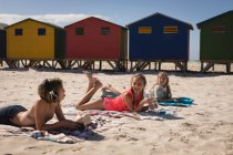 Happy siblings interacting while relaxing at beach on a sunny day — Stock Photo