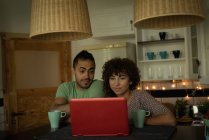 Couple à l'aide d'ordinateur portable tout en buvant le café à la maison — Photo de stock