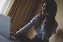 Mujer de negocios usando el ordenador portátil mientras habla por teléfono móvil en la habitación de hotel - foto de stock