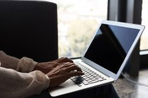Primer plano de la mujer de negocios madura usando el ordenador portátil en la oficina - foto de stock