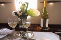 Бутылку шампанского со стеклом на столе в частном самолете — стоковое фото